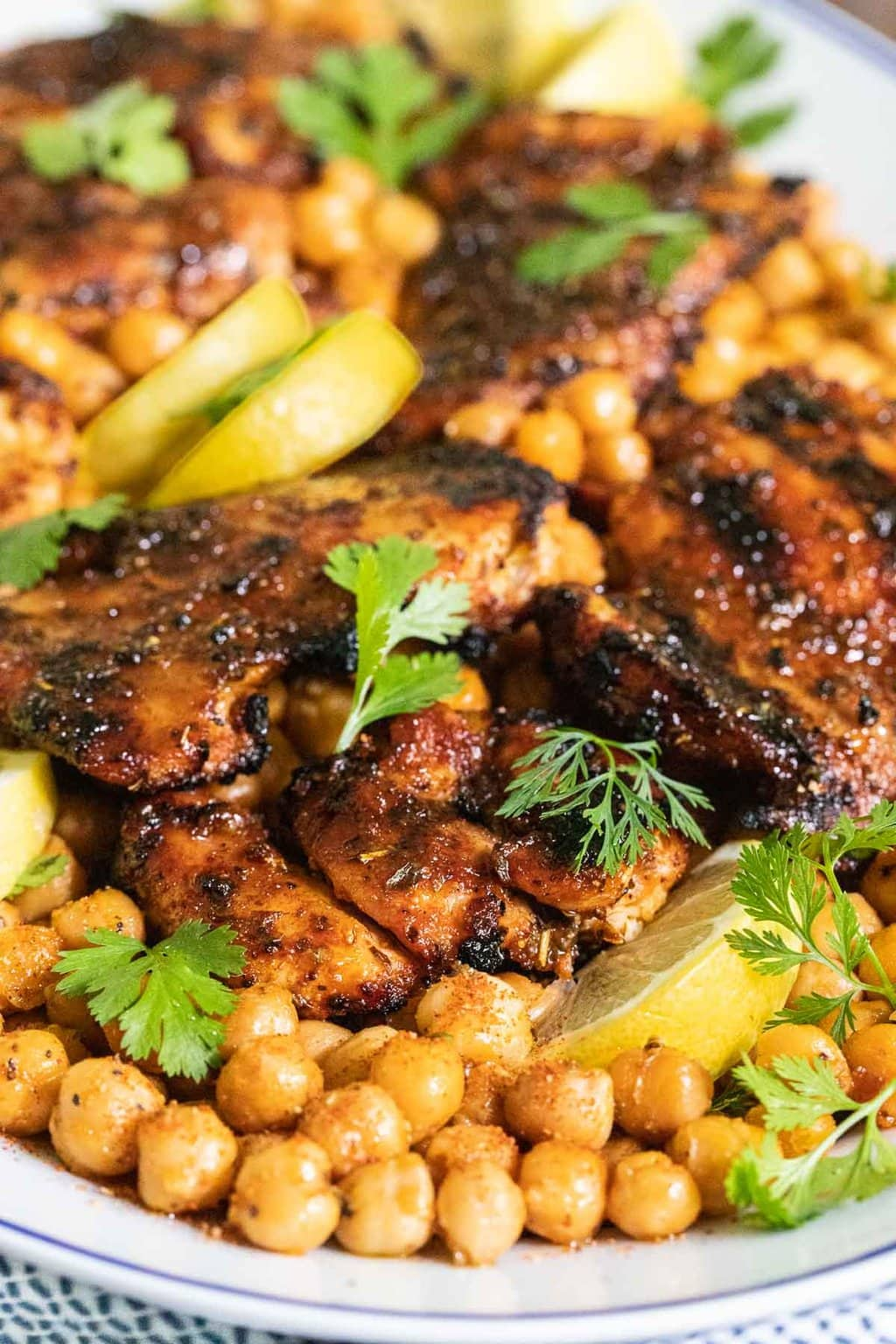 Vertical closeup photo of a serving platter of Charred Honey Lemon Grilled Chicken with Crispy Chickpeas.