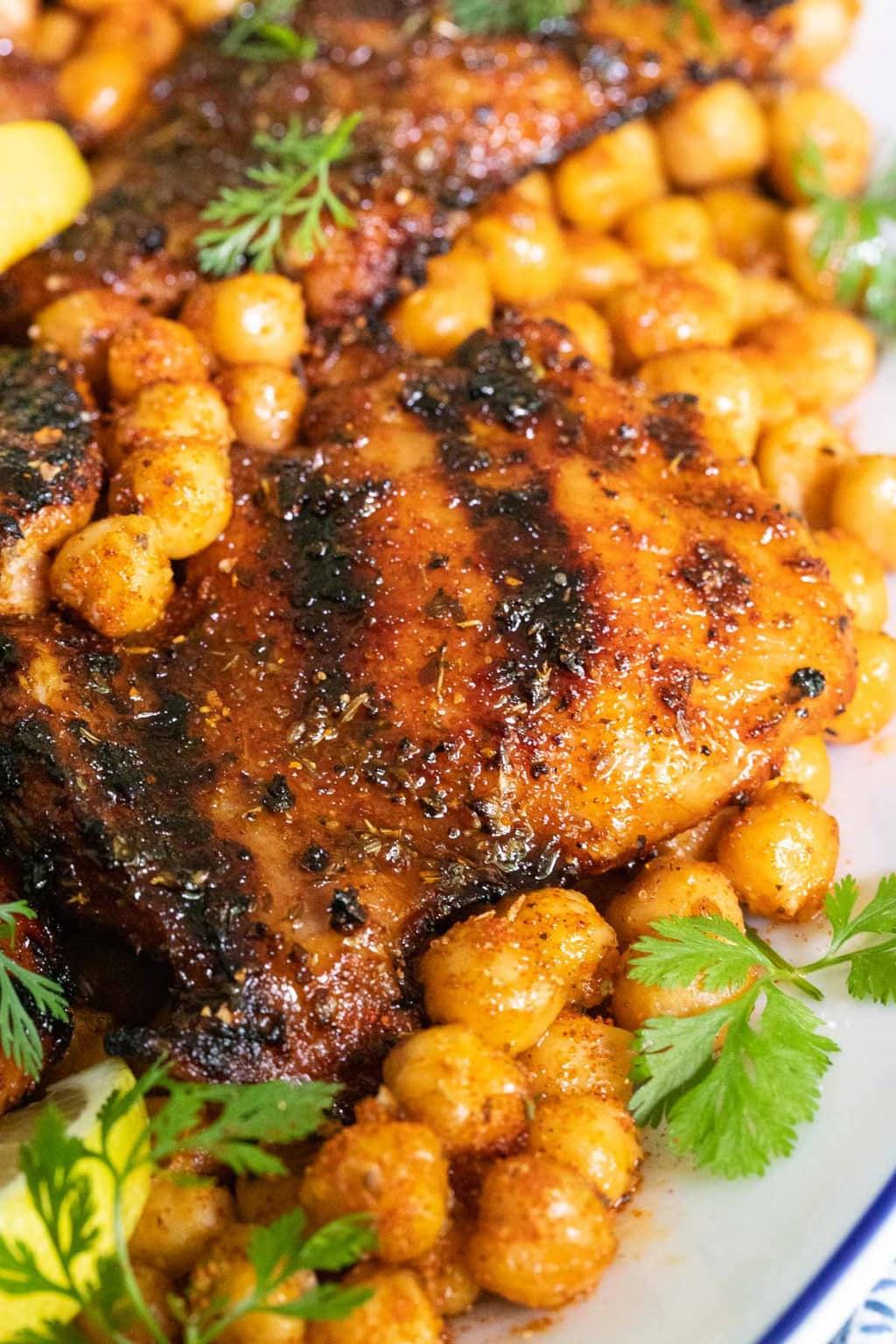 Ultra closeup vertical photo of Charred Honey Lemon Grilled Chicken with Crispy Chickpeas on a white serving platter.