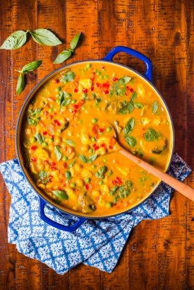 Overhead picture of Chicken, Carrot and Chickpea Coconut Curry in a blue saute pan on a wooden table
