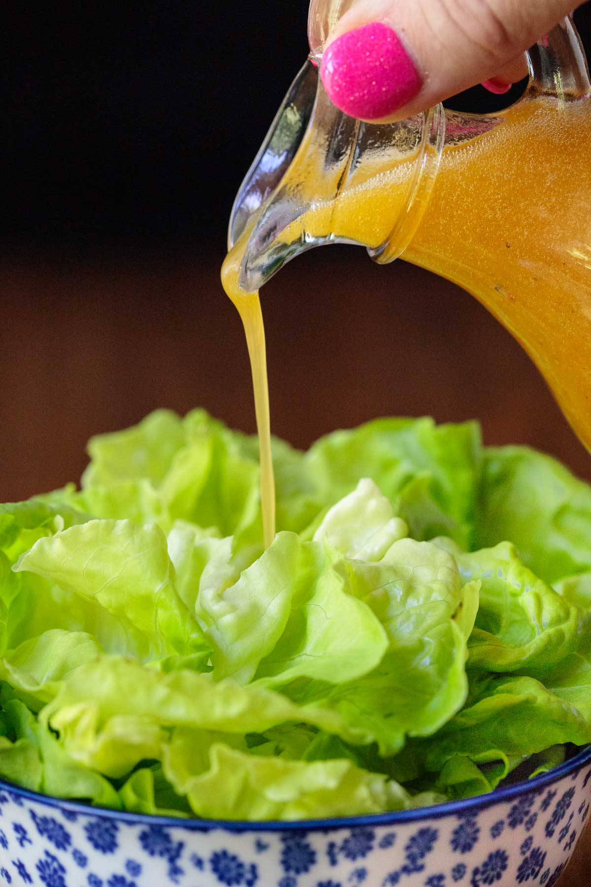 Pour shot of a small glass pitcher of Chili Lime Salad Dressing being poured over butter lettuce.