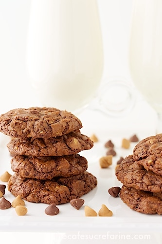 Two stacks of Chocolate Peanut Butter Toffee Cookies with glasses of milk in the background and chocolate chips in the foreground.