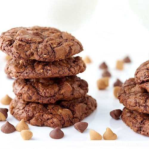 Photo of a stack of Chocolate Peanut Butter Toffee Cookies with glasses of milk in the background and chocolate chips in the foreground.