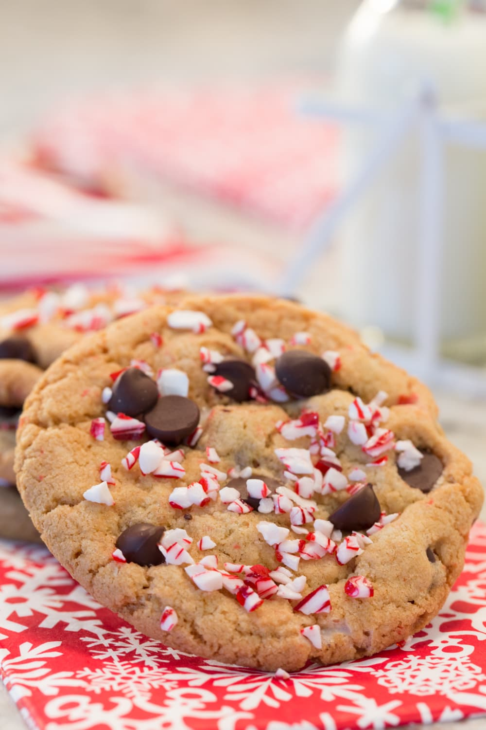 Vertical close up picture of chocolate chip candy cane cookies on a red and white napkin