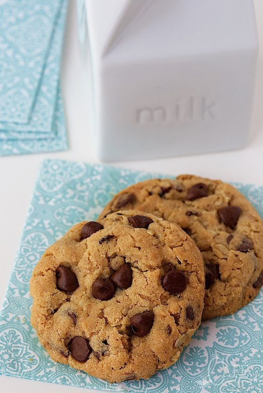 Photo of some Chocolate Chip Cherry Oatmeal Cookies on a turquoise and white napkin with a milk container and napkins in the background.