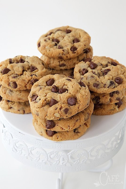 A photo of a white pedestal plate filled with Chocolate Chip Cherry Oatmeal Cookies.