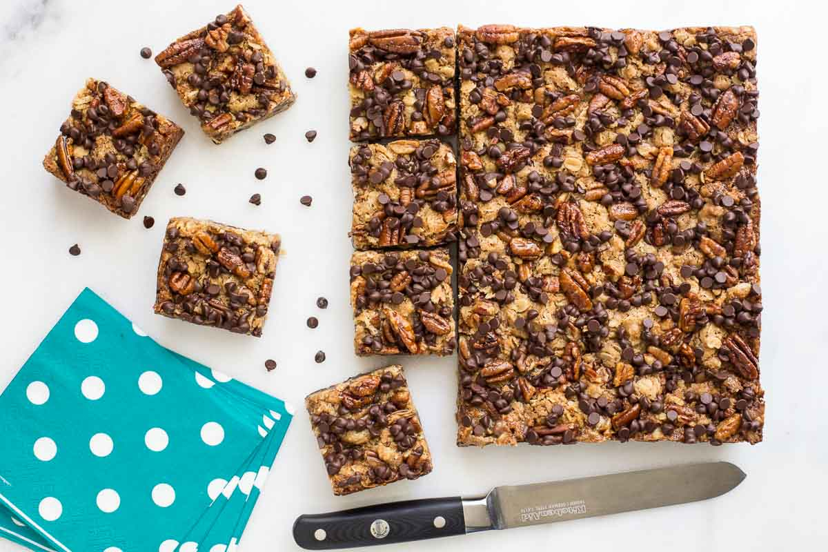 Overhead photo of a pan of Chocolate Chip Cherry Oatmeal Bars on a marble slab with a knife and turquoise napkins beside them.