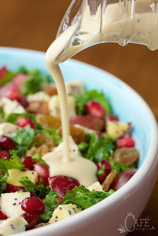 Close up picture of poppyseed dressing being poured on a chopped kale salad