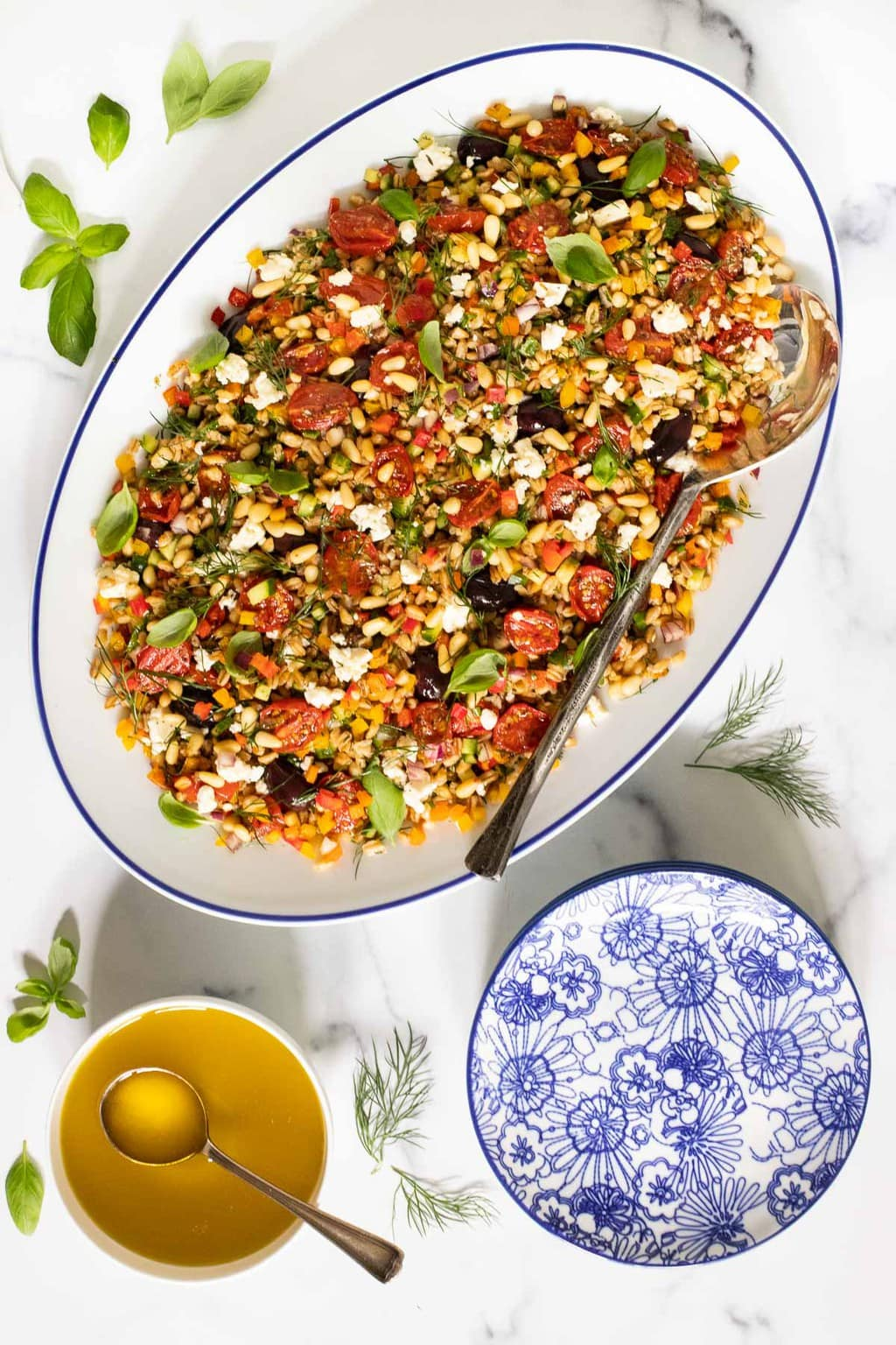 Vertical overhead picture of chopped mediterranean farro salad in a white oval platter with dressing