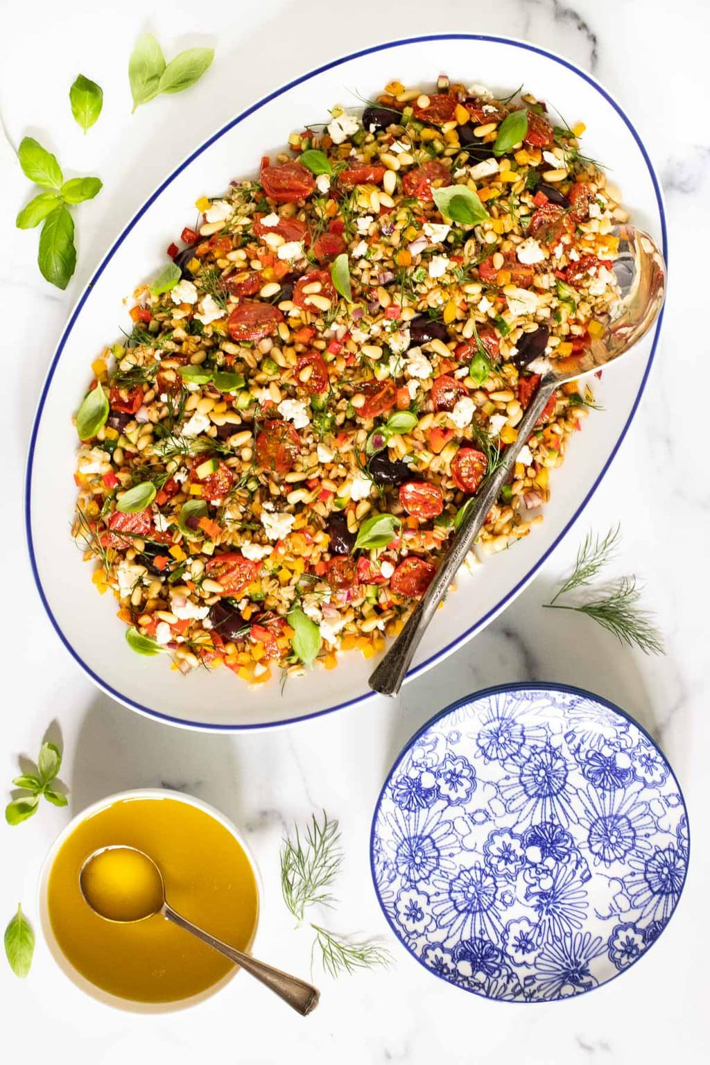 Vertical overhead photo of a Chopped Mediterranean Farro Salad in a white oval serving platter surrounded by basil and dill garnishes and a bowl of dressing.