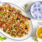 Horizontal overhead photo of a Chopped Mediterranean Farro Salad on a white oval serving platter surrounded by basil and dill garnishes.