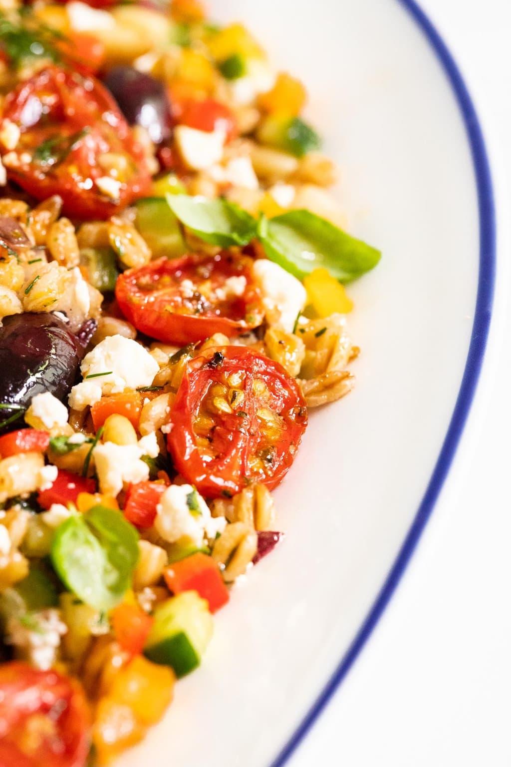 Vertical closeup photo of a Chopped Mediterranean Farro Salad in a white serving platter with blue trim.