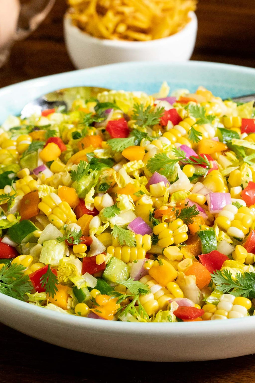 Vertical closeup photo of a Chopped Mexican Street Corn Salad in a white and turquoise serving dish.
