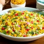 Horizontal closeup photo of Chopped Mexican Street Corn Salad in a white and turquoise serving bowl.