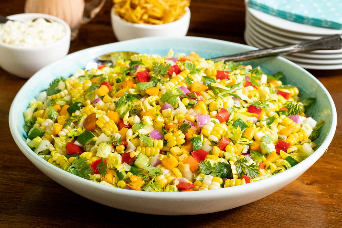 Horizontal closeup photo of Chopped Mexican Street Corn Salad in a white and turquoise serving bowl on a wood table.