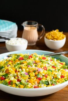 Vertical photo of a Chopped Mexican Street Corn Salad in a white an turquoise serving bowl.