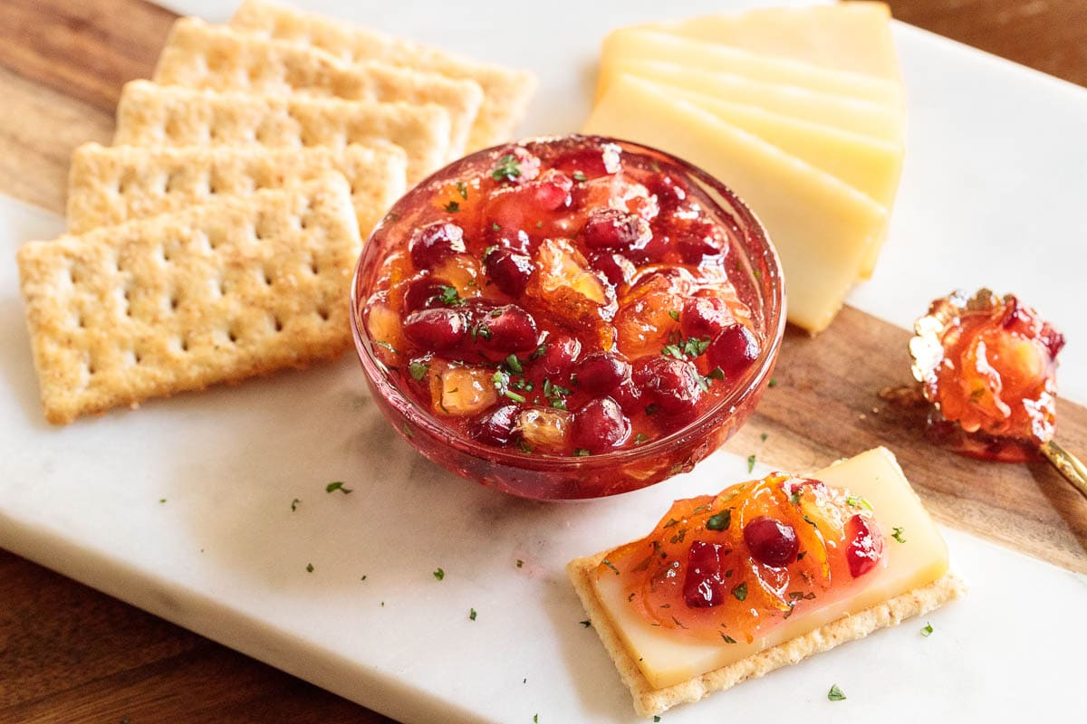 Photo of a glass dish filled with Easy Orange-Cranberry Christmas Marmalade surrounded by cheese and crackers.