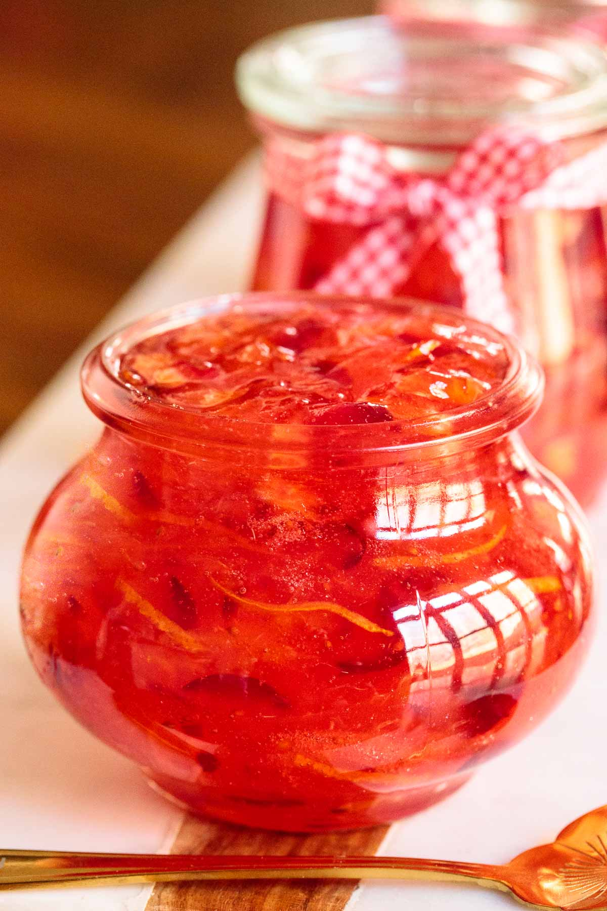 Closeup photo of a Weck glass canning jar filled with Easy Orange-Cranberry Christmas Marmalade.