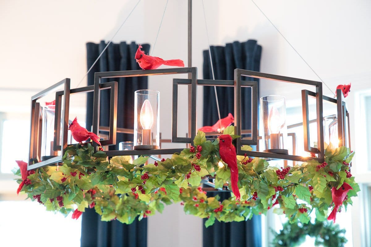 Closeup photo of a holiday-themed dining room chandelier, festooned with bright red cardinals and green garland.