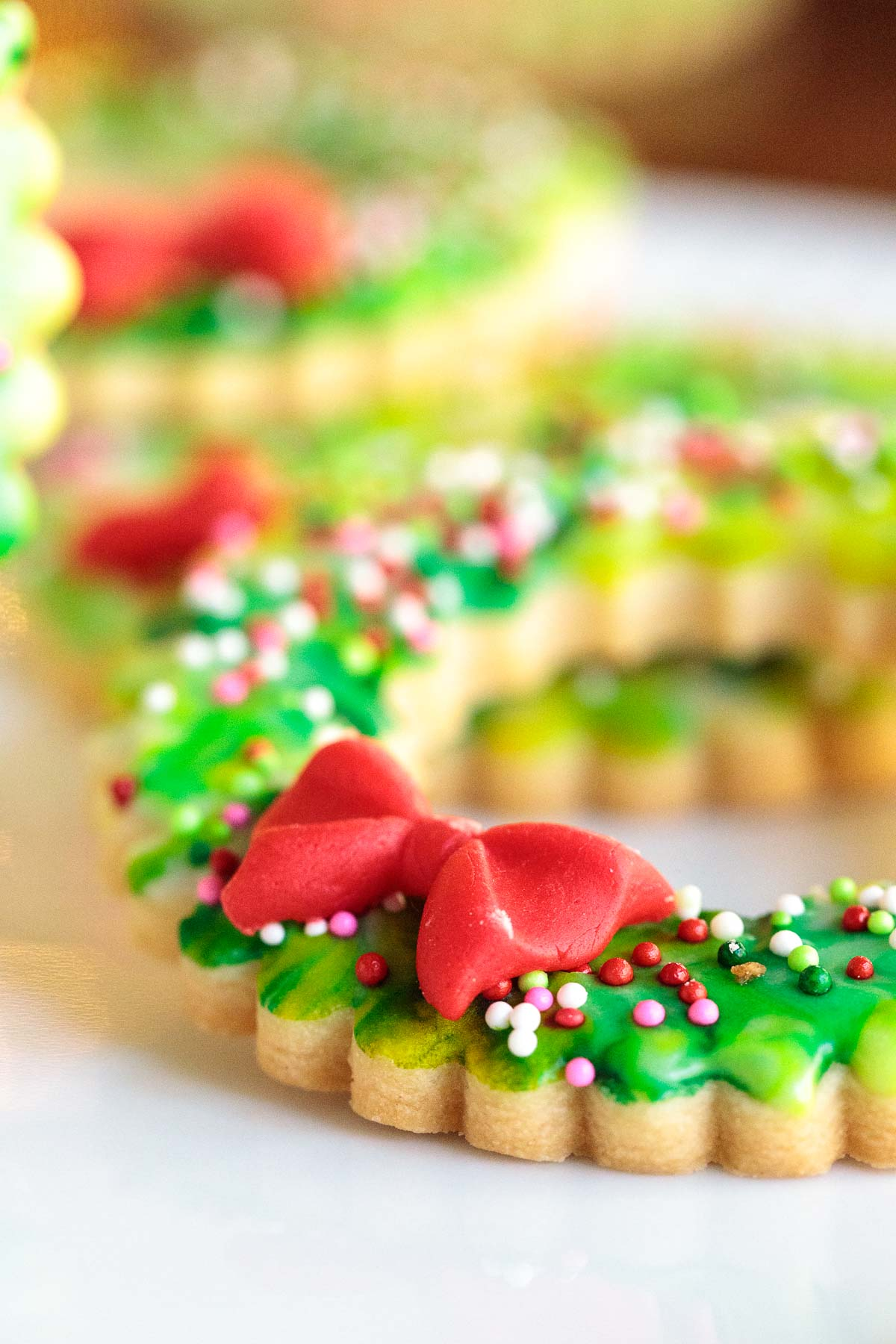 Ultra closeup photo of a fondant bow on a Christmas Wreath Shortbread Cookie.