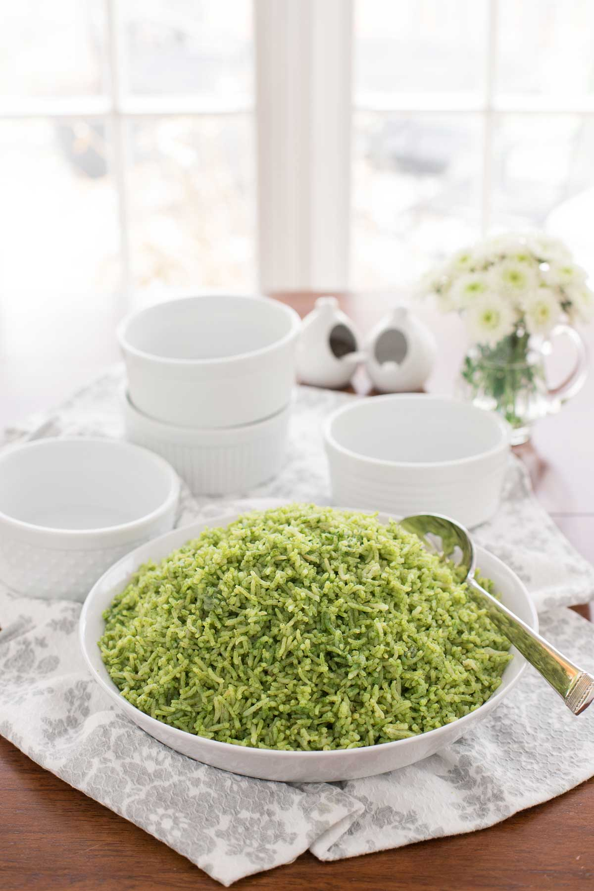Table photo of a dish of Cilantro Rice (Arroz Verde) surrounded by a table setting and bowls for serving the rice.