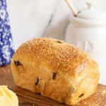 Vertical picture of Cinnamon Raisin Brioche bread on a wooden cutting board