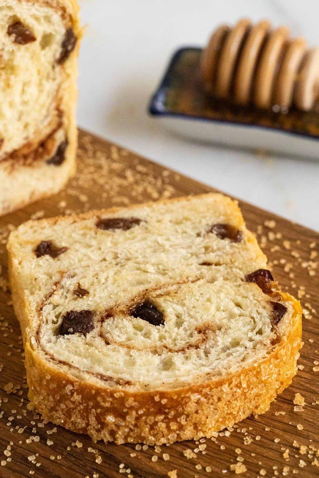 Closeup vertical photo of a slice of Cinnamon Raisin Brioche Bread on a cutting board.