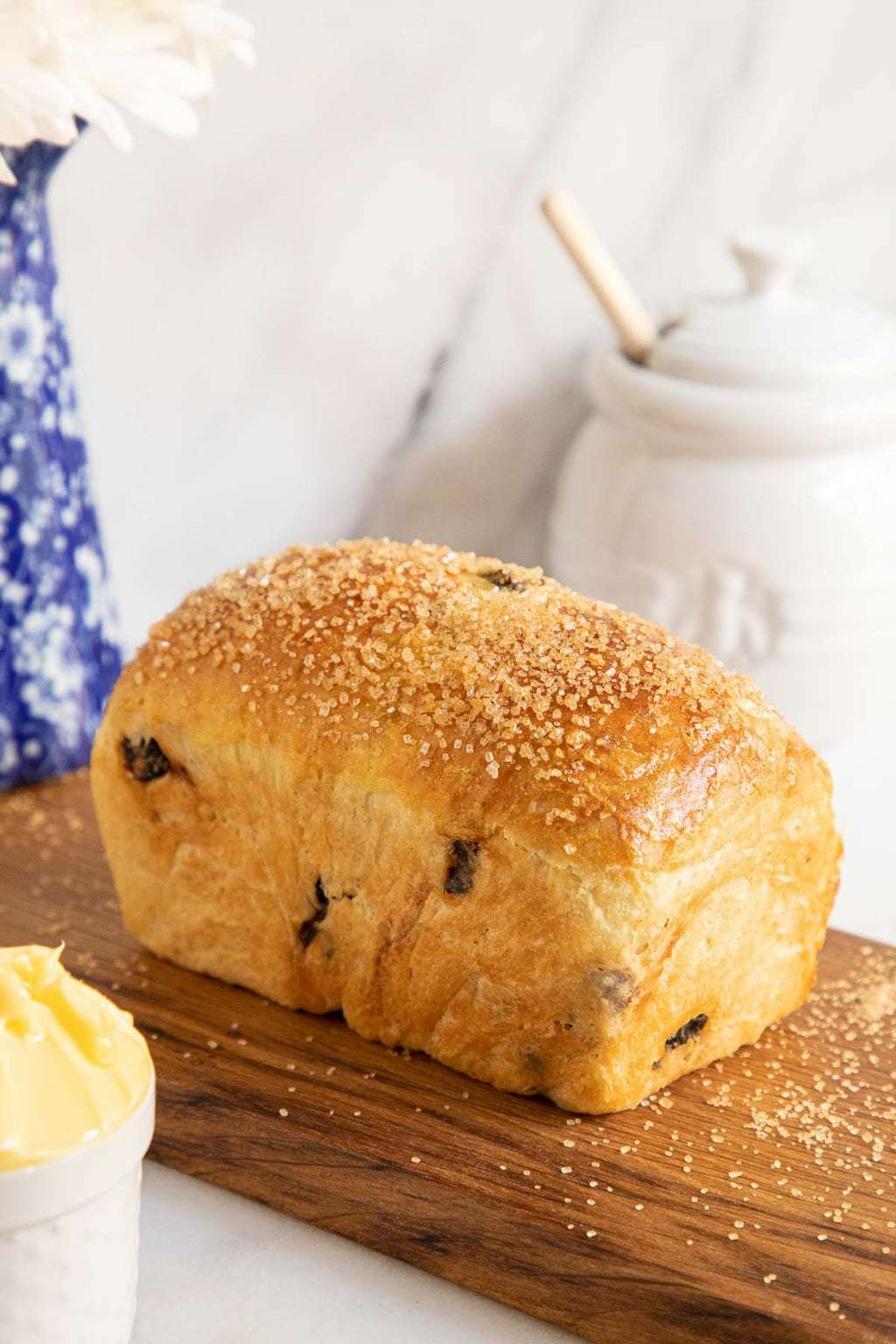 Vertical picture of Cinnamon Raisin Brioche bread on a wooden cutting board