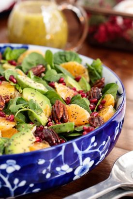 Vertical picture of clementine avocado spinach salad in a blue and white bowl