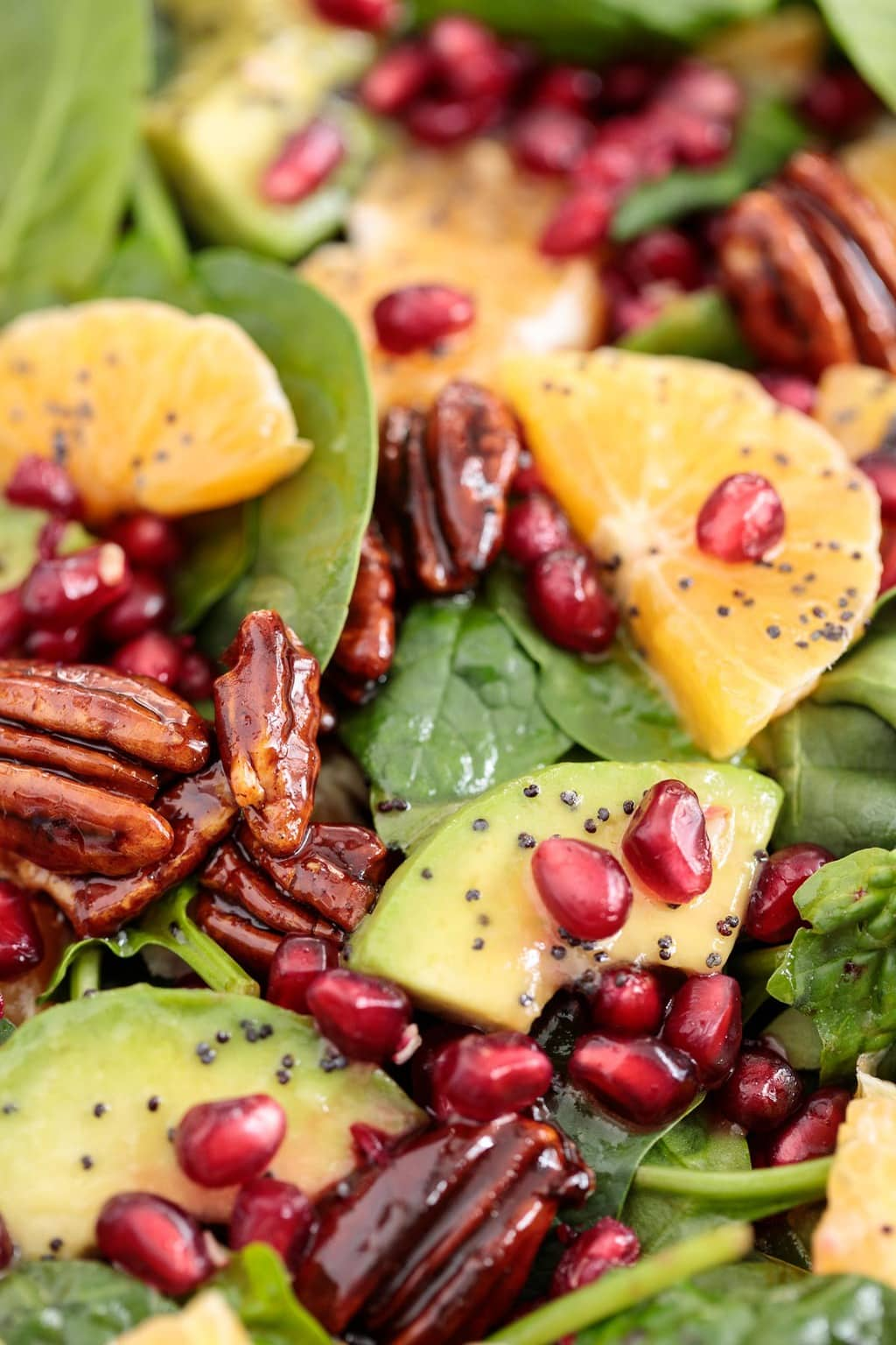 Ultra closeup photo of a Clementine Avocado Spinach Salad; featuring clementines, pomegranates, and candied pecans.