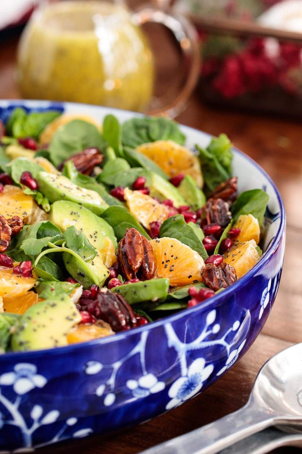 Photo of a blue and white patterned bowl of Clementine Avocado Spinach Salad on a wood table with a glass jar of vinaigrette in the background.