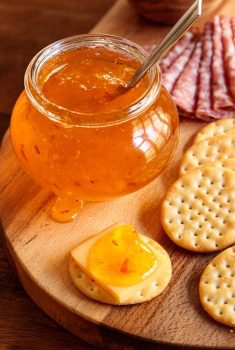 Vertical closeup photo of Clementine Pepper Jelly with cheese and crackers.
