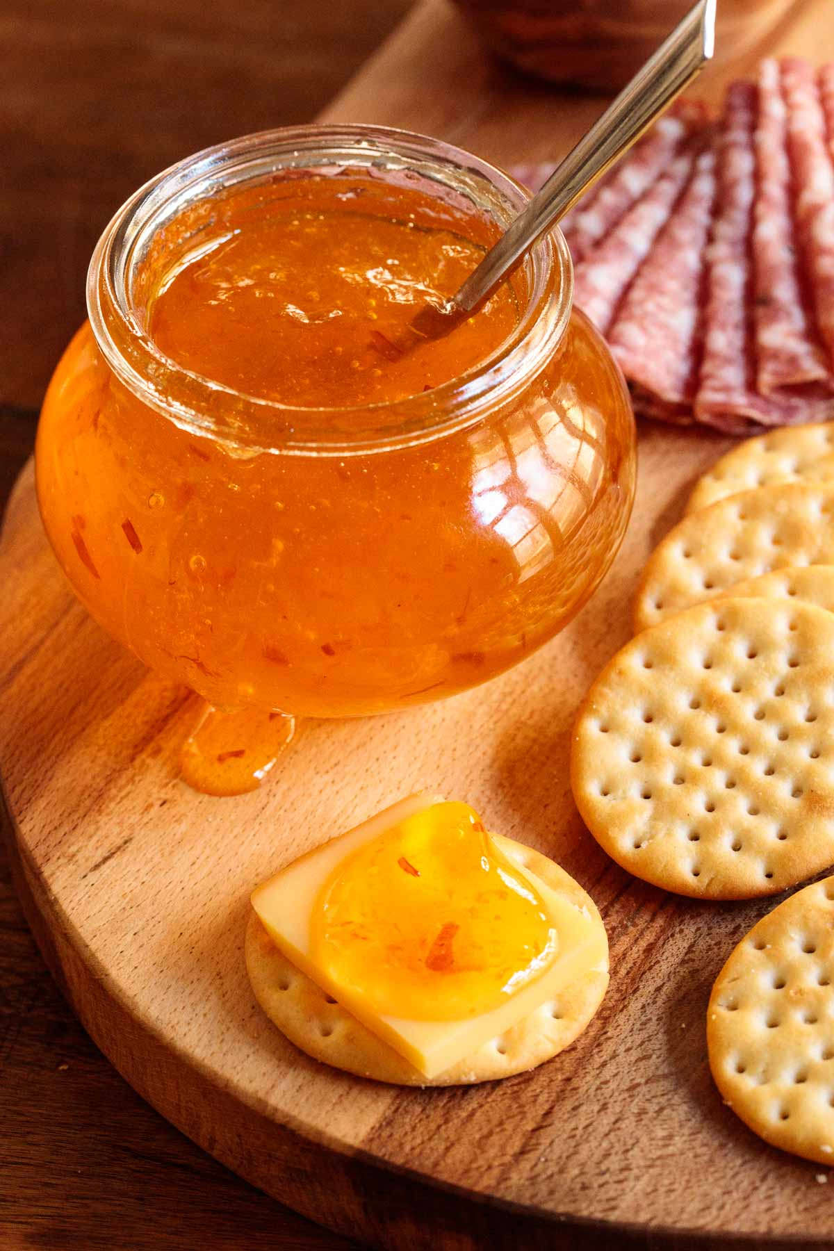 Vertical photo of Clementine Pepper Jelly with cheese and crackers on a wood appetizer board.