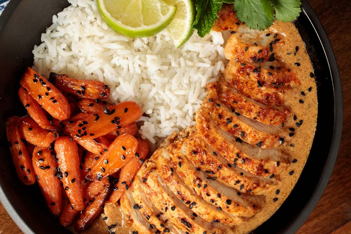 Overhead closeup photo of an individual serving bowl of Coconut Braised Chicken Breasts with sides of white rice and honey ginger charred carrots garnished with lime wedges.