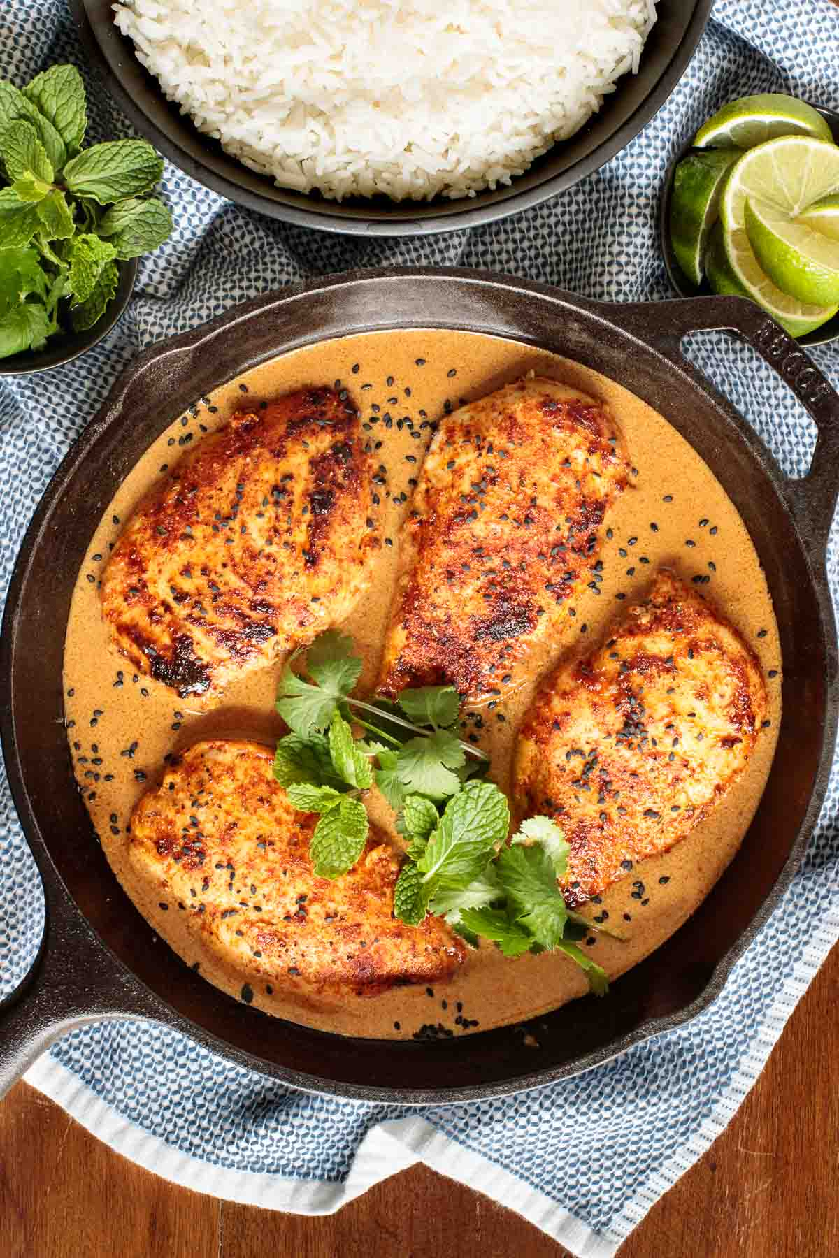 Overhead photo of a cast iron skillet filled with Coconut Braised Chicken Breasts.