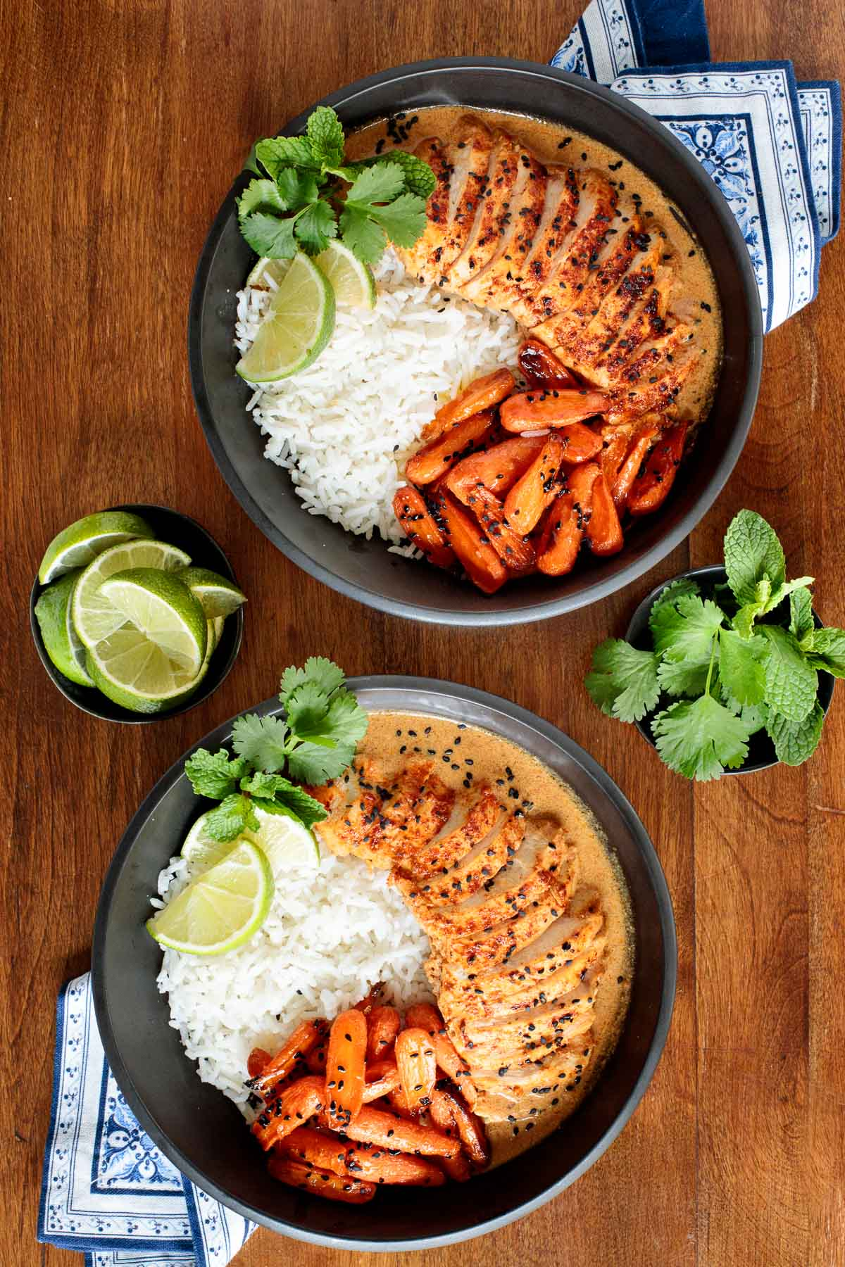 Overhead photo of two individual serving bowls of Coconut Braised Chicken Breasts served with honey ginger charred carrots and white rice.