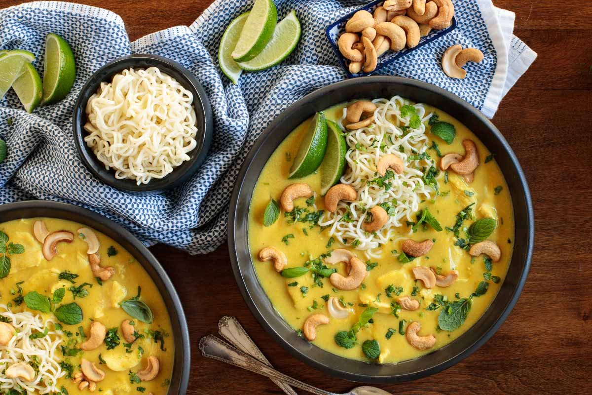 Overhead photo of two black bowls of Coconut Curry Chicken Ramen on a wood table surrounded by lime wedges, cashews and a small bowl of ramen noodles.