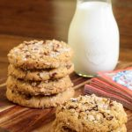 Vertical picture of coconut pecan cookies stacked on a wooden platter with milk
