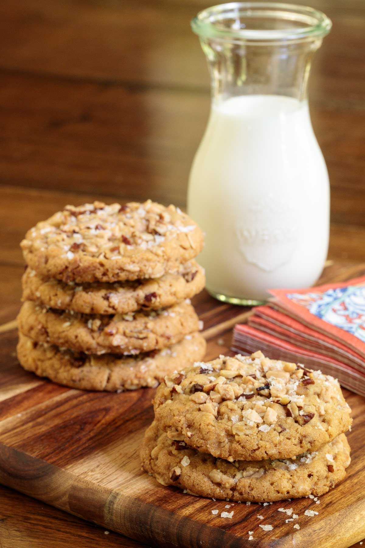 Vertical photo of Coconut Pecan Toffee Cookies stacked on a wooden platter with a pitcher of milk in the background.