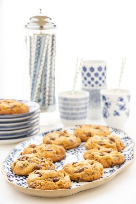 Vertical photo of a batch of Crumbl Chocolate Chip Cookies on a blue and white platter with glasses of milk in the background.