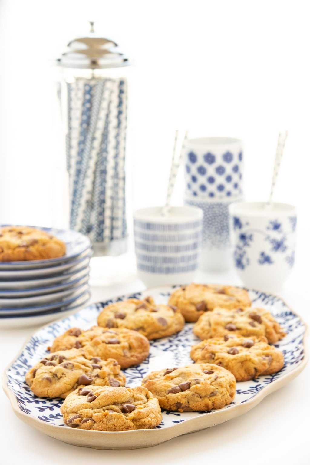 Vertical photo of Crumbl Chocolate Chip Cookies on a white and blue patterned platter with cups of milk an a straw dispenser in the background.