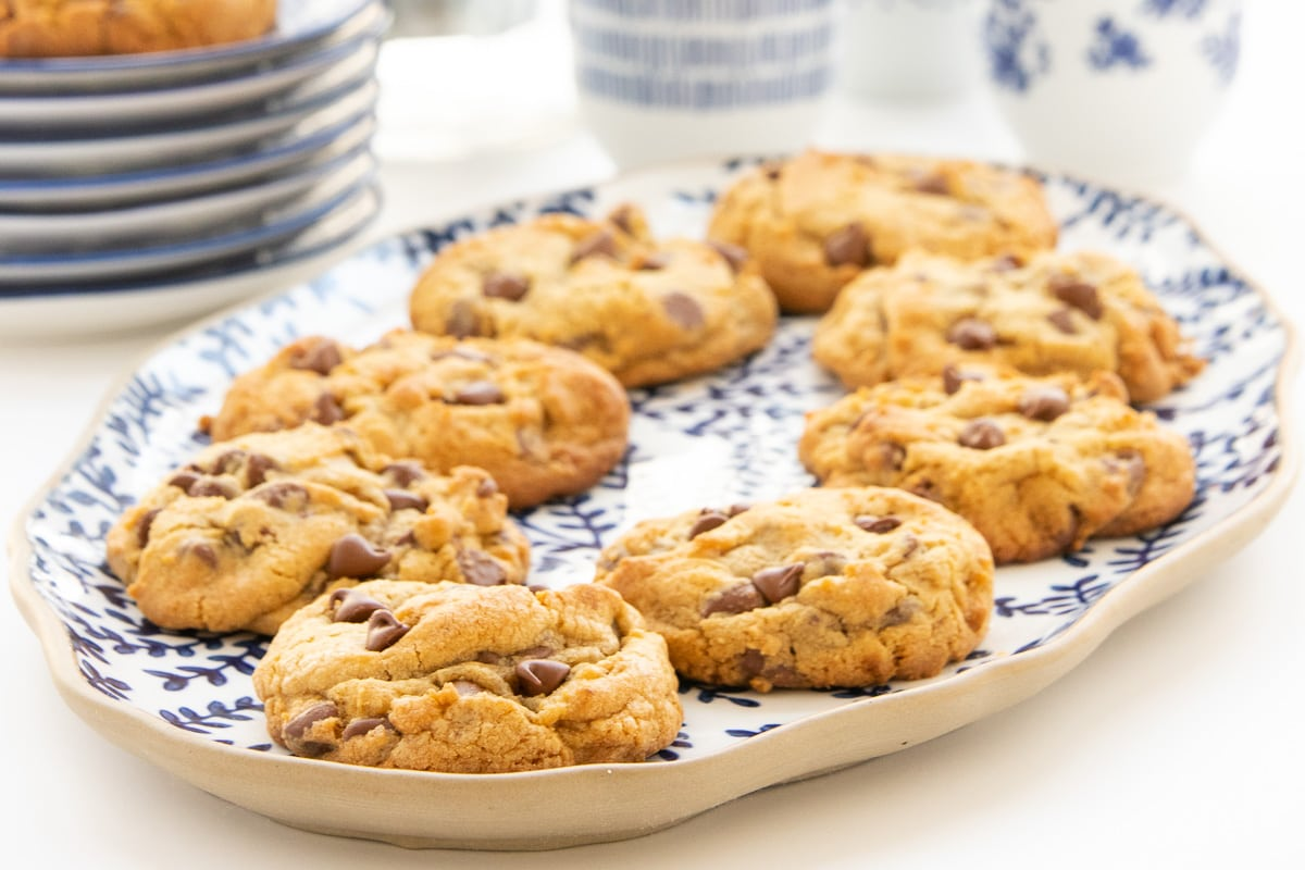 Horizontal closeup photo of a batch of Copycat Crumbl Chocolate Chip Cookies on a blue and white serving platter.