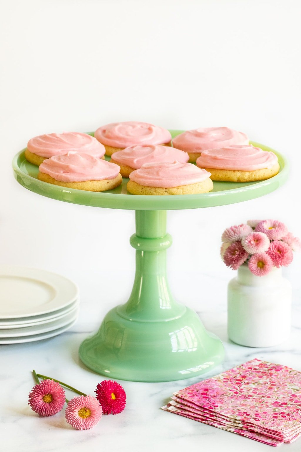 Vertical photo of a batch of Copycat Crumbl Sugar Cookies on a jade green marble pedestal presentation stand.