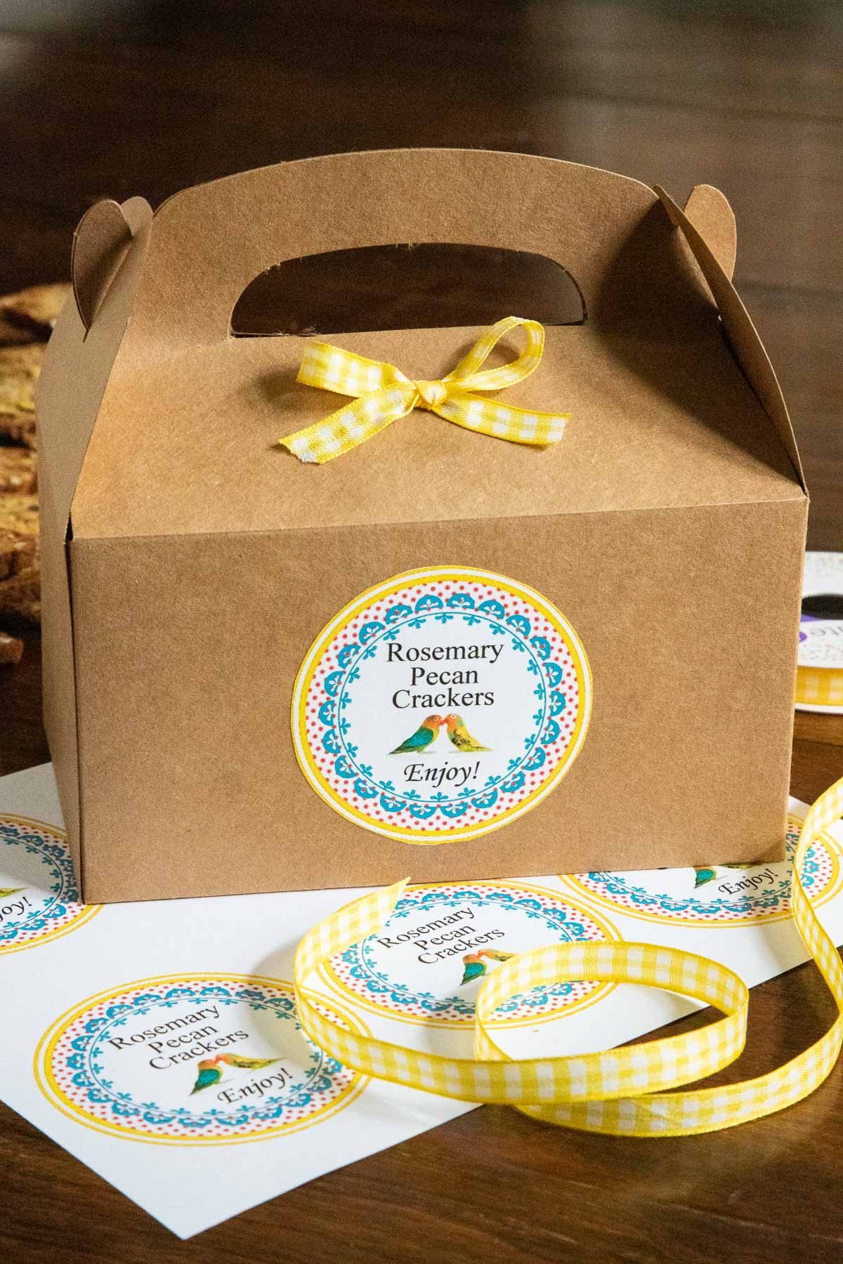 Vertical photo of a gift box filled with Copycat Rosemary Pecan Raincoast Crackers and decorated with a custom label for gift giving.