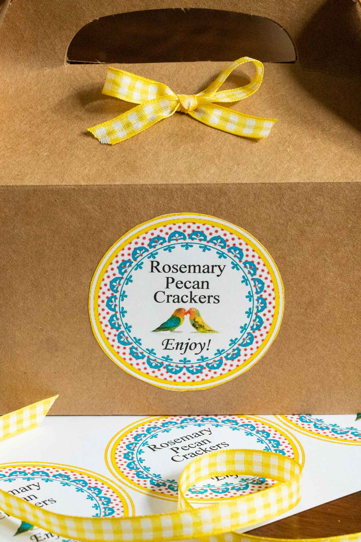 Closeup vertical photo of the Rosemary Pecan Crackers custom label on a brown gift box.