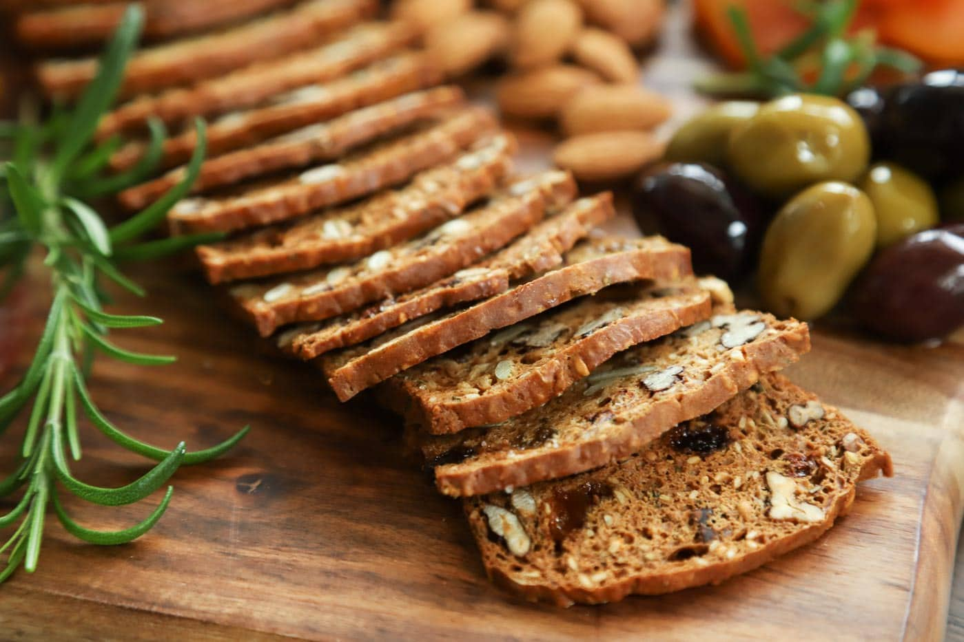 Photo of a row of Rosemary Raisin Pecan Crisps on a wood appetizer serving board with olives, almonds and a sprig of rosemary.