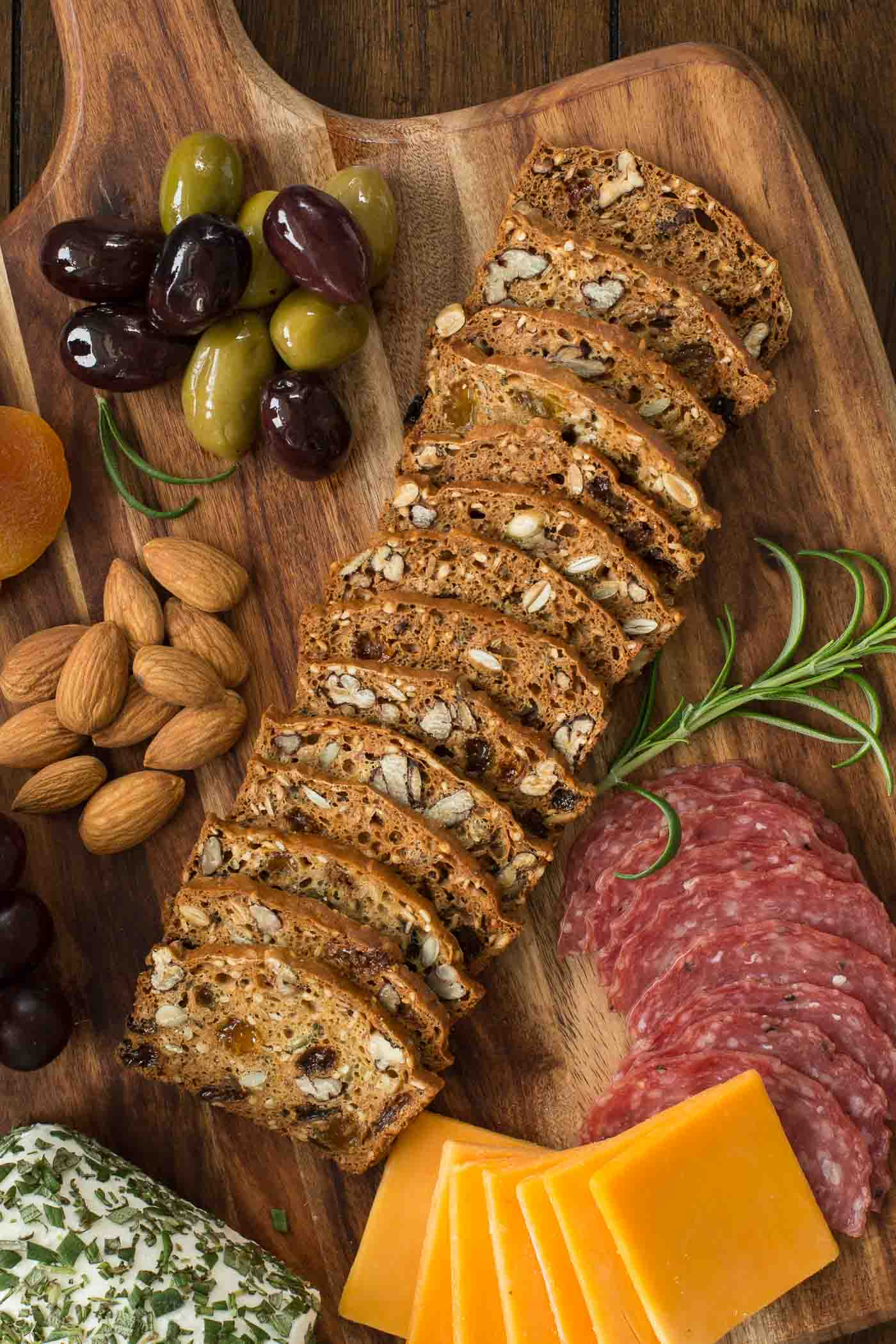 Overhead view of raincoast crackers on a cheeseboard with olives and nuts. Holiday appetizers post.