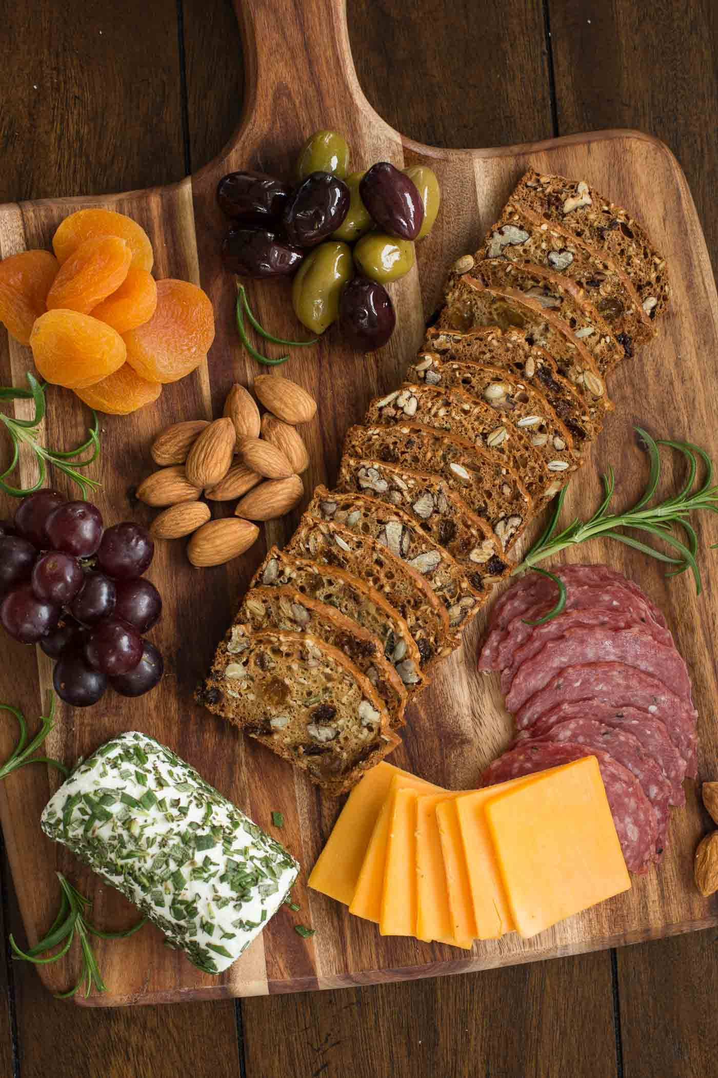 Vertical overhead picture of Rosemary Raisin Pecan Crisp Crackers on a wooden cutting board with cheese and salami