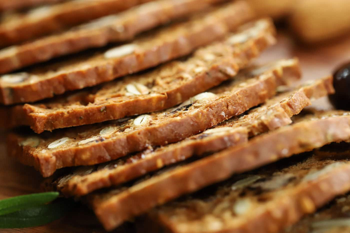 Extreme horizontal closeup photo of thinly cut Copycat Rosemary Pecan Raincoast Crackers.