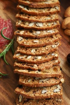 Vertical close up picture of raincoast crackers on a wooden cheeseboard