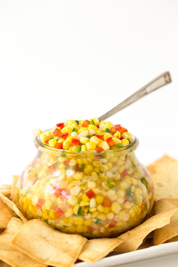 Vertical photo of a glass jar willed with Trader Joe's Corn and Chile Salsa and a spoon in the salsa. Pita chips are on a plate surrounding the jar.